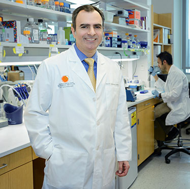 Dr. Ralph DeBerardinis standing in the lab