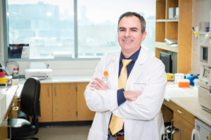 Dr. Ralph DeBerardinis stands in his lab, arms crossed.